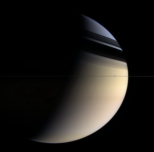 Tiny Enceladus orbits outside Saturn's rings